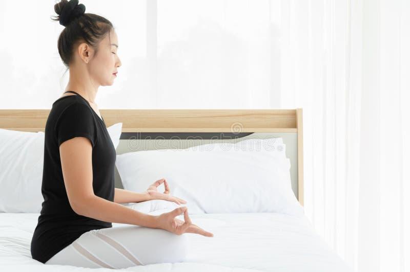 De Aziatische vrouw het praktizeren yoga, die Half Lotus doen stelt met mudragebaar op bed in de slaapkamer stock afbeelding