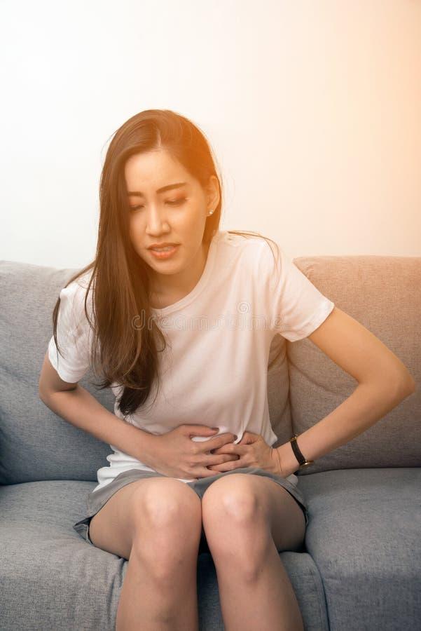 De Aziatische vrouw houdt haar maag met beide handen Maag of pijn tijdens menstruatie wordt verstoord die stock afbeeldingen