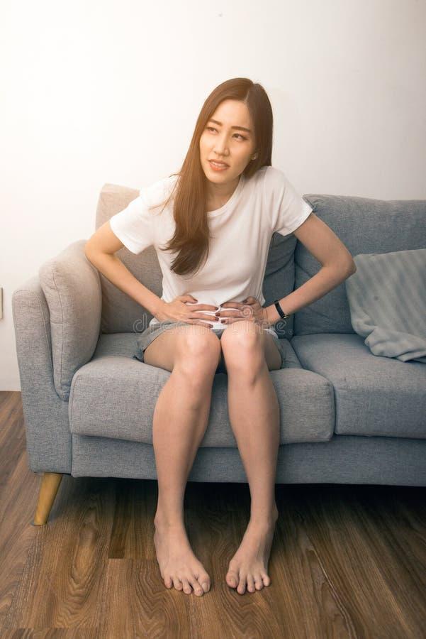 De Aziatische vrouw houdt haar maag met beide handen Maag of pijn tijdens menstruatie wordt verstoord die royalty-vrije stock afbeelding