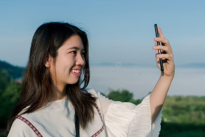 De Aziatische vrouw neemt een selfietelefoon, op het toeristengebied achter de mist en de bergen met het glimlachen neemt een gez royalty-vrije stock foto's
