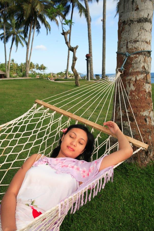 De Aziatische vrouw ontspant bij strand stock afbeelding