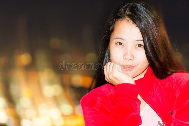 De Aziatische vrouw rust haar kin op hand stock afbeeldingen