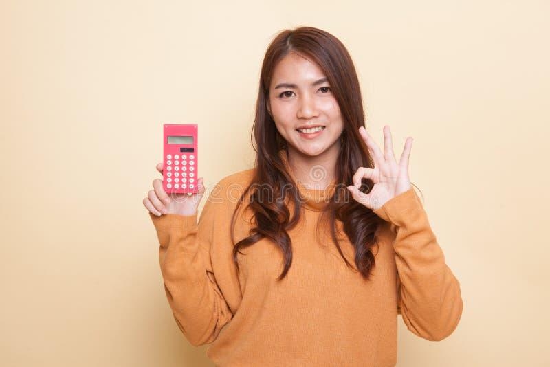 De Aziatische vrouw toont o.k. met calculator royalty-vrije stock afbeeldingen