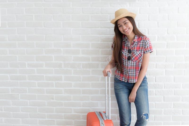 De Aziatische vrouw treft om op witte bakstenen muur, Lifest te reizen voorbereidingen stock afbeelding
