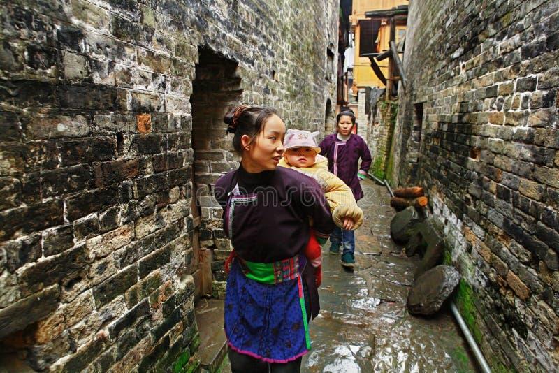 De Aziatische vrouw vervoert baby achter de rug in landelijk China. royalty-vrije stock foto's