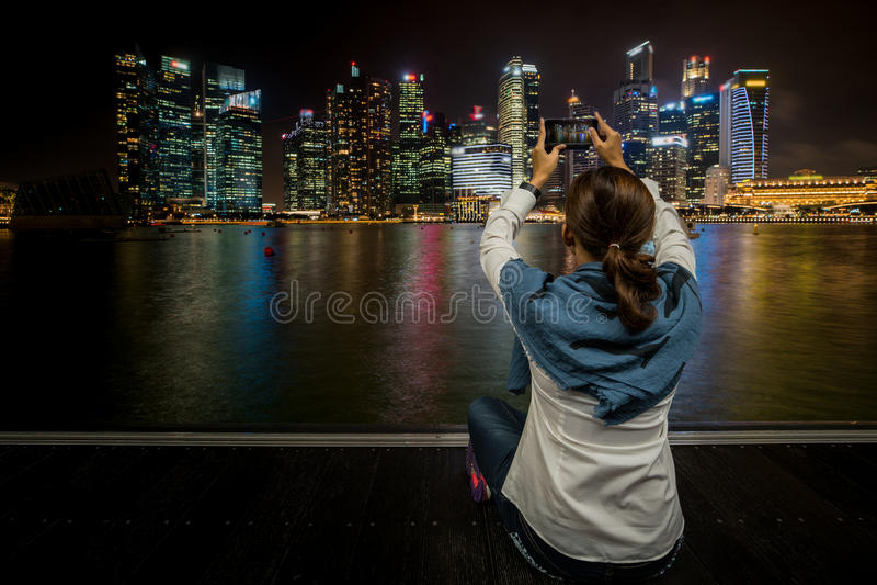 De Aziatische vrouw zit en neemt stads scape foto door mobiele telefoon stock fotografie