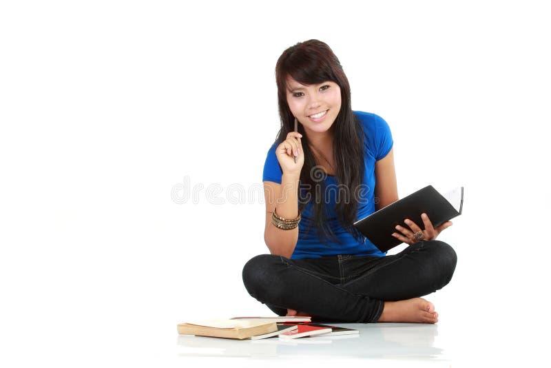 De Aziatische vrouw zit met een boek stock foto