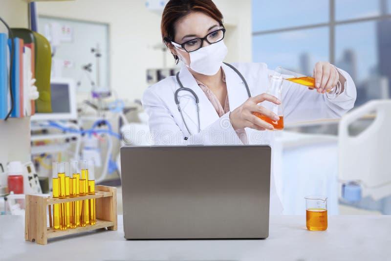De Aziatische vrouwelijke arts analyseert vloeistof bij kliniek royalty-vrije stock fotografie