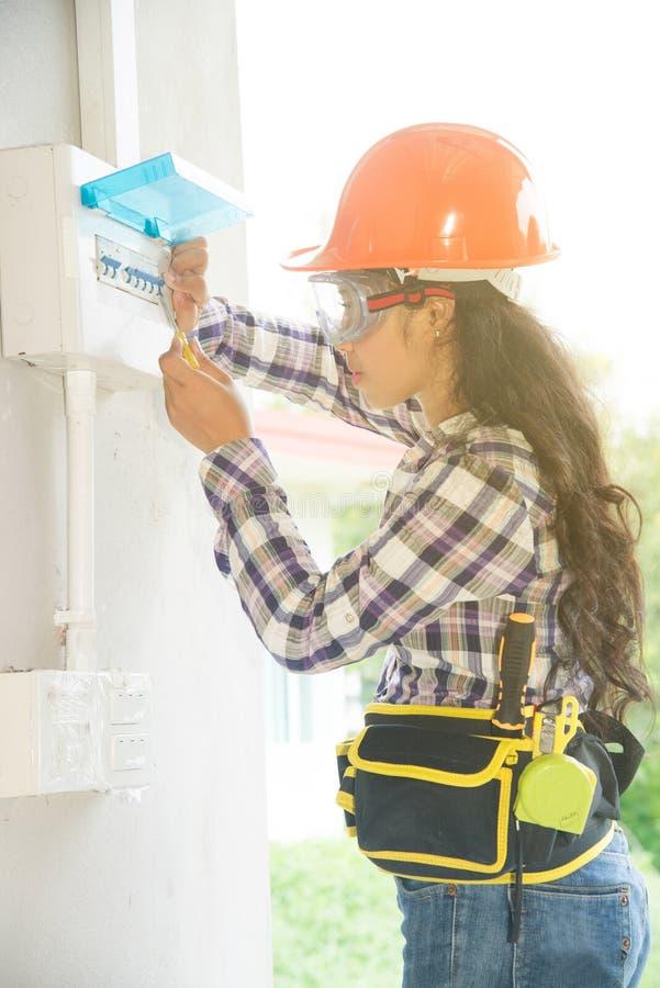 De Aziatische vrouwelijke Elektricien of Ingenieurscontrole of inspecteert Elektrosysteemstroomonderbreker royalty-vrije stock fotografie