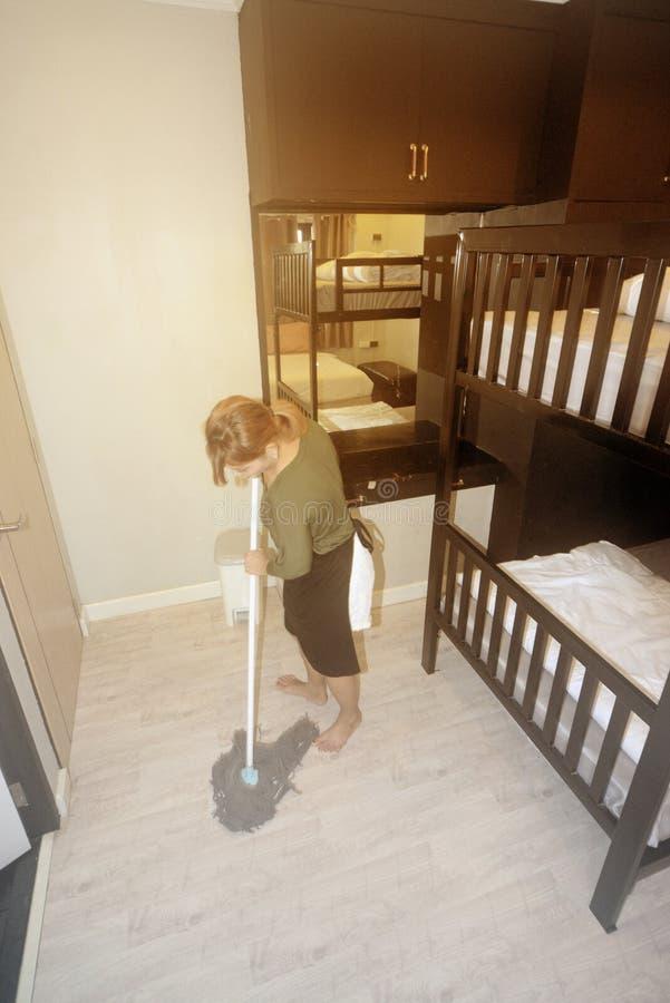 De Aziatische vrouwelijke meisje schoonmakende dienst met zwabber schoonmakende vloer stock foto