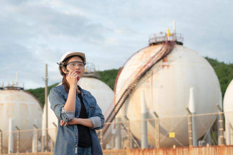 De Aziatische vrouwelijke radioverbindingen van de ingenieursgreep om het werk binnen de olieraffinaderij te controleren royalty-vrije stock fotografie