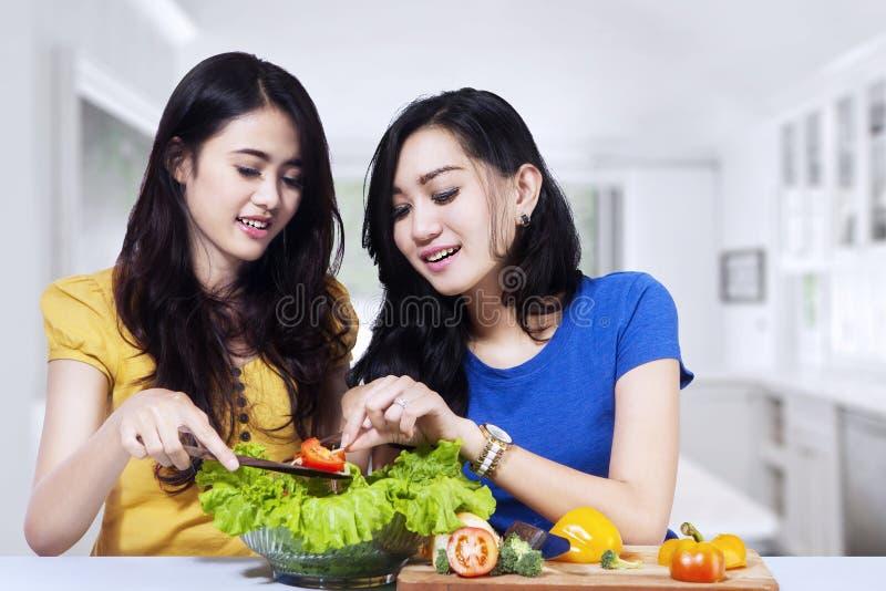 De Aziatische vrouwen bereiden samen salade voor royalty-vrije stock afbeeldingen