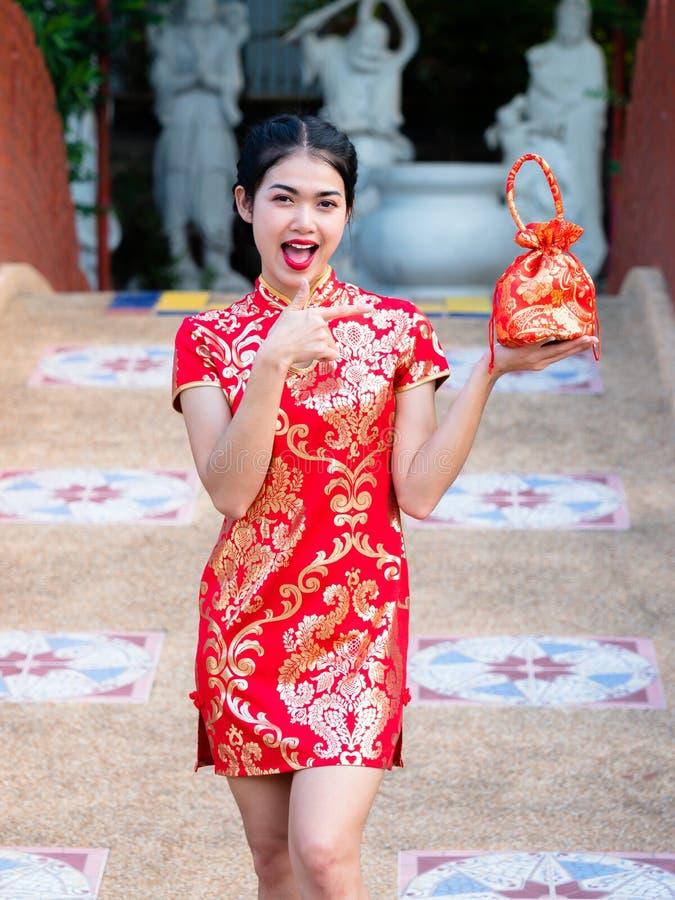 De Aziatische vrouwen in Chinese nationale kostuums houden groetzak voor het Chinese Nieuwjaar royalty-vrije stock foto