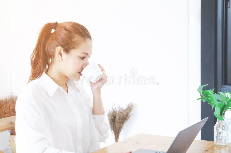 De Aziatische vrouwen die een wit overhemd dragen werkt en nipt koffie royalty-vrije stock afbeelding