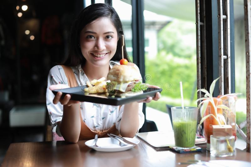 De Aziatische vrouwen die en gelukkig en genoten van etend hamburgers bij koffie en restaurant ontspannen tijd glimlachen stock afbeelding