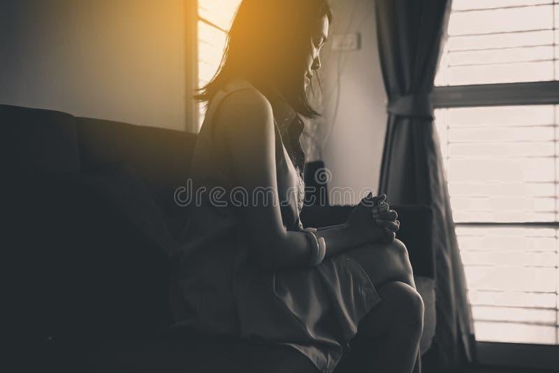 De Aziatische vrouwen die in livin zitten verzorgen thuis, Vrouwelijke het voelen hoofdpijn en verward probleem in het persoonlij stock fotografie