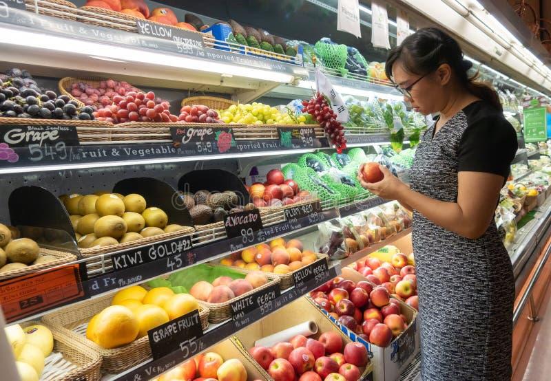 De Aziatische vrouwen die in supermarkt of kruidenierswinkel winkelen slaan op royalty-vrije stock afbeelding