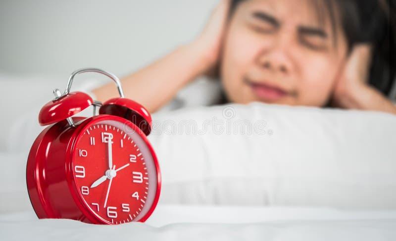 De Aziatische vrouwen ontwaken van slaap Zijn de handen van haar orenbecau royalty-vrije stock afbeeldingen