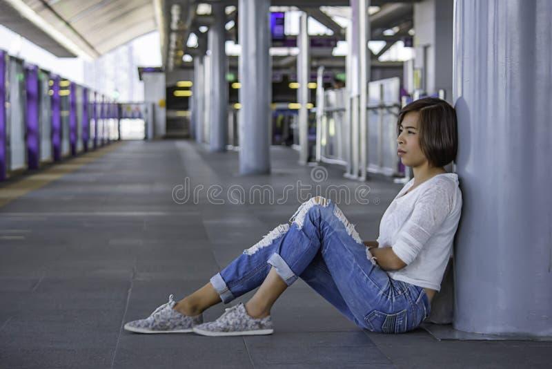 De Aziatische vrouwen zitten op de post vloer Achtergrond onscherpe van Skytrain stock afbeelding