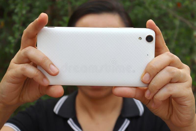 De Aziatische vrouwenholding en het gebruiken van smartphone tonen achterkant stock foto
