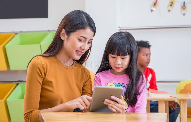 De Aziatische vrouwenleraar onderwijst studente met tabletcomputer in klaslokaal bij concept van het kleuterschool het peuter, On stock foto's
