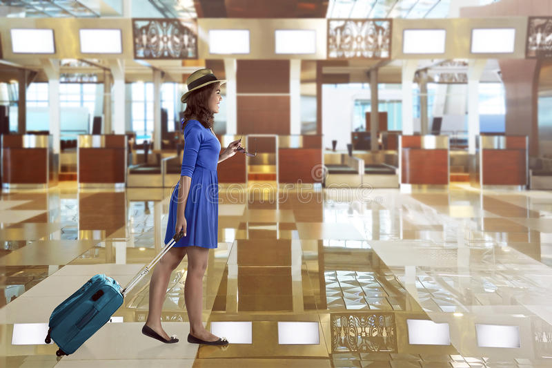 De Aziatische vrouwenreis draagt alleen koffer in de luchthaven stock afbeeldingen