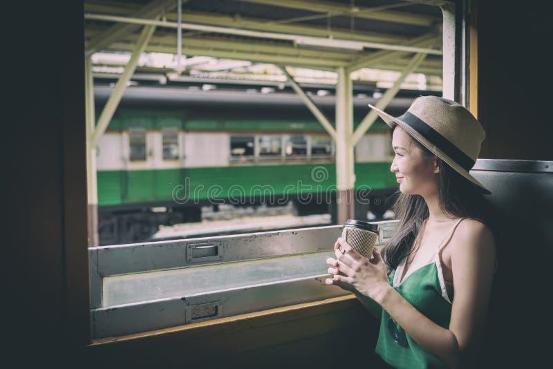 De Aziatische vrouwenreiziger heeft het drinken koffie in de trein met geluk bij Hua Lamphong-post in Bangkok, Thailand royalty-vrije stock afbeelding