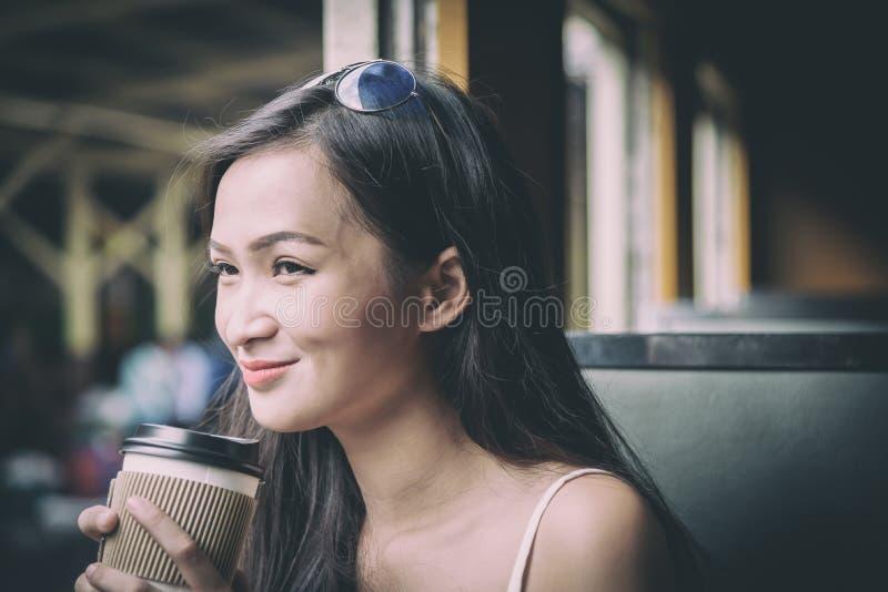 De Aziatische vrouwenreiziger heeft het drinken koffie in de trein met geluk bij Hua Lamphong-post in Bangkok, Thailand stock fotografie