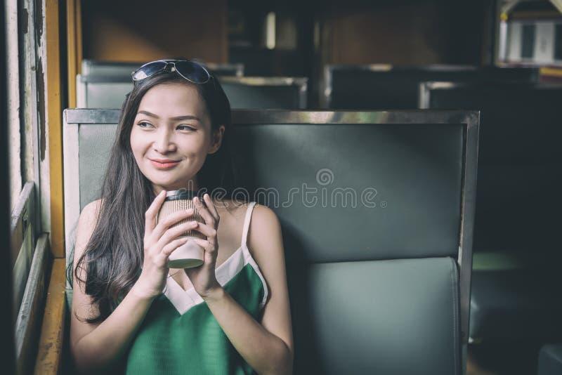 De Aziatische vrouwenreiziger heeft het drinken koffie in de trein met geluk bij Hua Lamphong-post in Bangkok, Thailand royalty-vrije stock foto