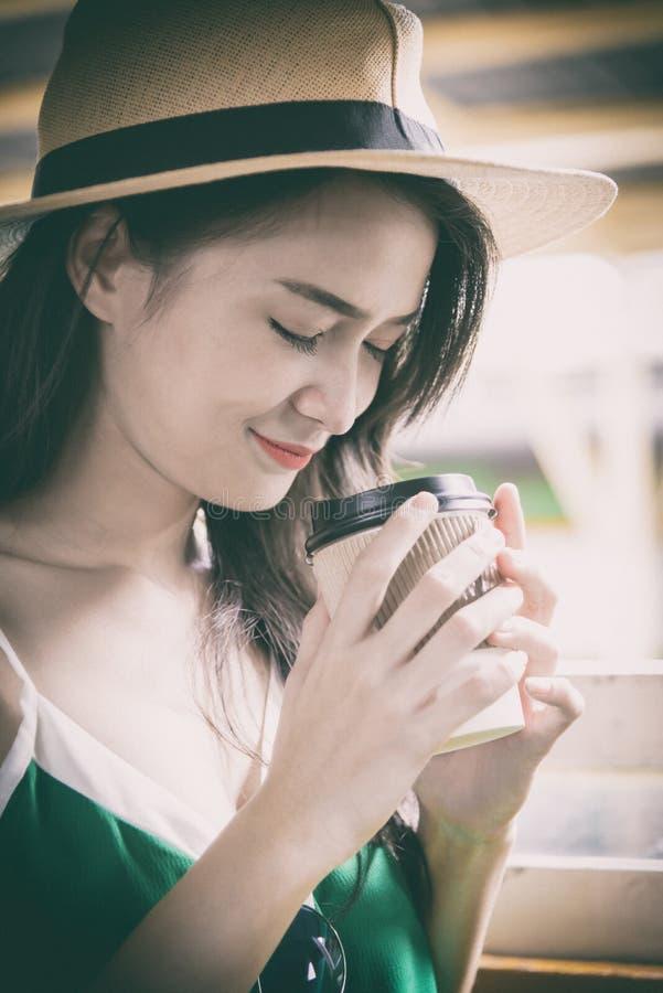 De Aziatische vrouwenreiziger heeft het drinken koffie in de trein met geluk bij Hua Lamphong-post in Bangkok, Thailand stock afbeelding