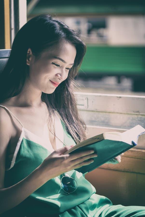 De Aziatische vrouwenreiziger heeft het lezen van een boek in de trein met geluk bij Hua Lamphong-post in Bangkok, Thailand stock afbeelding
