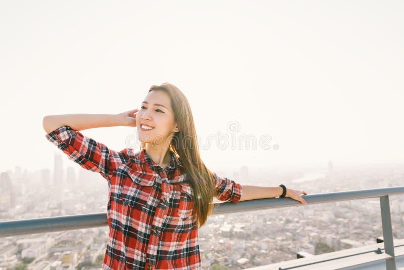 De Aziatische vrouwenreiziger of de student glimlacht en geniet van mening bij de bouw van dak, die zonsondergang gelijk maken On stock foto's