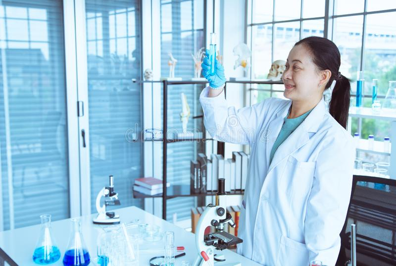 De Aziatische vrouwenwetenschapper bekijkt reageerbuis in haar hand met blauwe handschoen voor analyse blauwe vloeistof royalty-vrije stock foto's