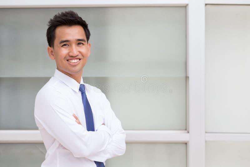 De Aziatische zakenman status bewapent gekruist en glimlachend royalty-vrije stock afbeelding
