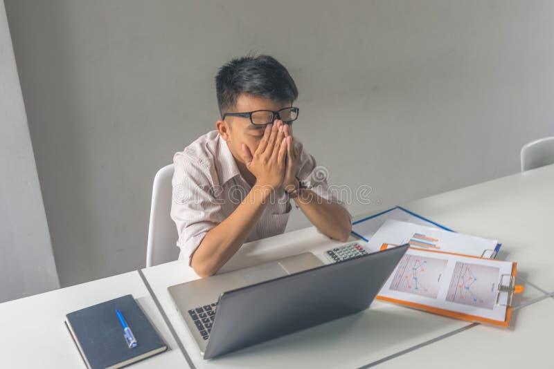 De Aziatische zakenman voelt hoofdpijn, die en uitgeput in de bedrijfsruimte wordt vermoeid stock afbeeldingen
