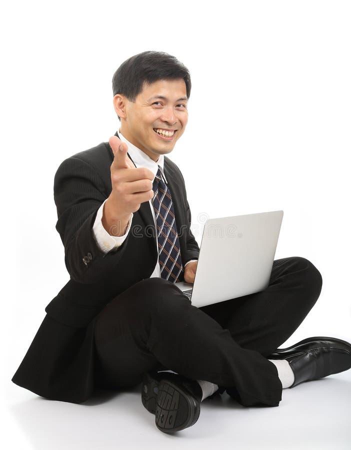 De Aziatische zakenman zit en speelt laptop royalty-vrije stock foto
