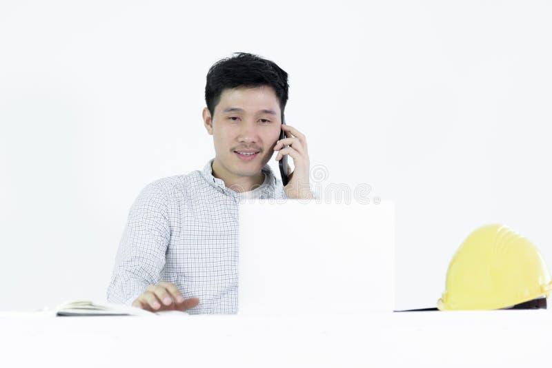 De Aziatische zitting van de het salarismens van de werknemersingenieur bij bureau en het spreken w royalty-vrije stock afbeelding