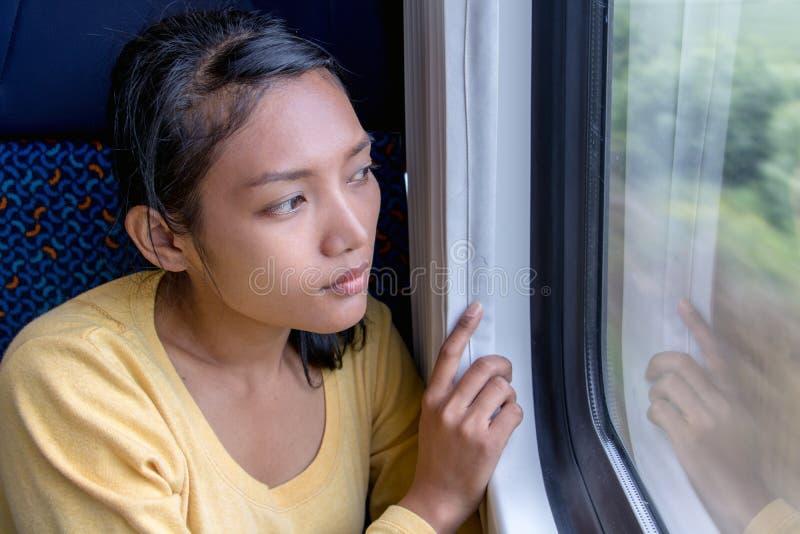 De Aziatische zitting van de vrouwenreiziger door trein stock afbeelding