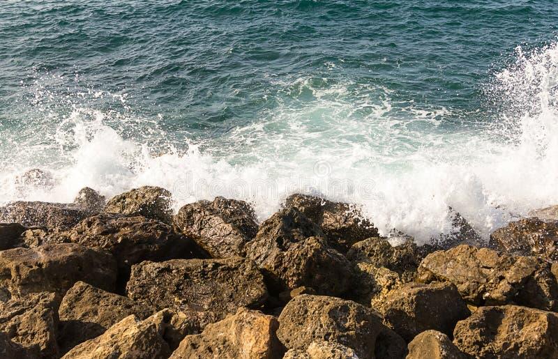 De azuurblauwe overzeese witte golf is gebroken over de kust bruine stenen Griekenland royalty-vrije stock foto's