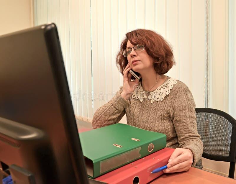 De bärande anblickarna för affärskvinnan talar av telefonen som ser i datorbildskärmen royaltyfri foto
