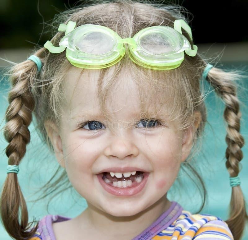 De baby in beschermende brillen zwemt pool. stock fotografie