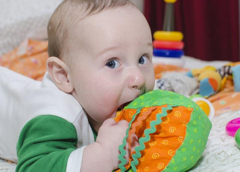 De baby bijt stuk speelgoed, close-up stock afbeelding