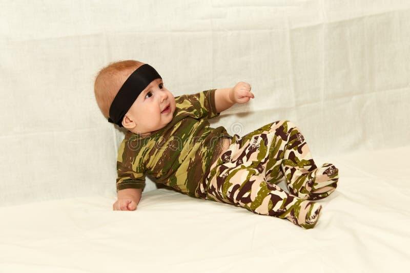 De baby in camouflagekleren op een witte achtergrond stock afbeelding