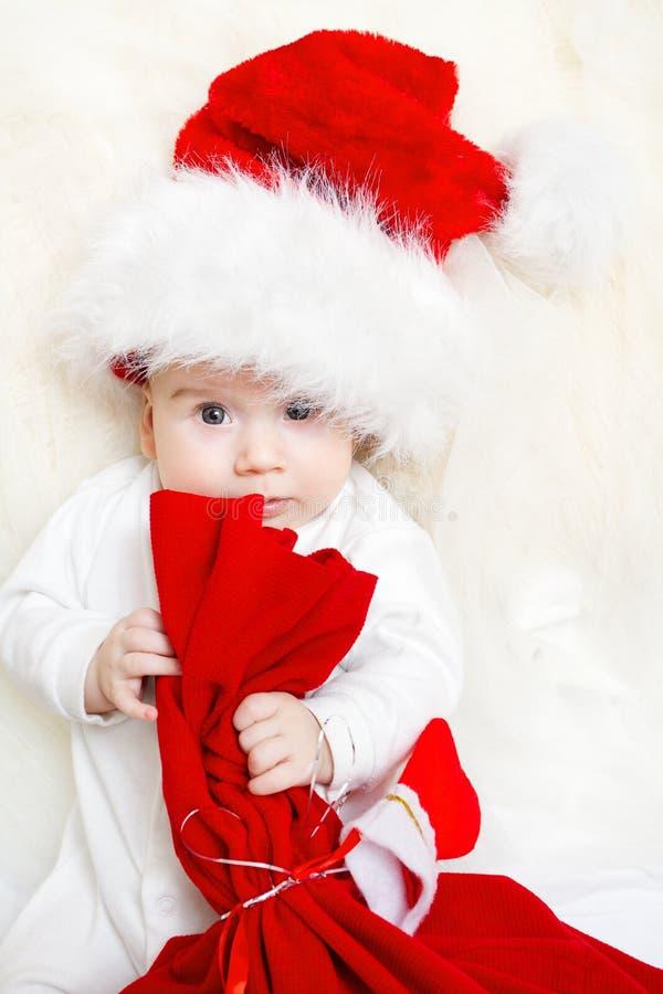 De baby die van Kerstmis rode zak in hoed houdt stock foto