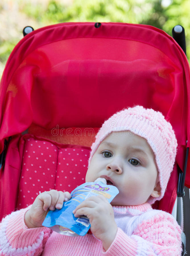 De baby eet een puree van een supermarkt stock afbeeldingen