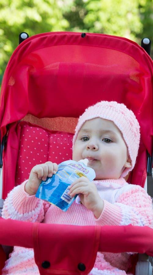 De baby eet een puree van een supermarkt stock fotografie
