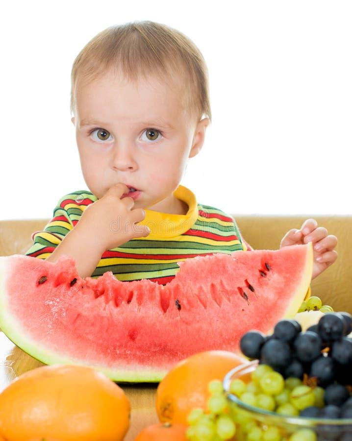 De baby eet fruit op een witte achtergrond stock afbeeldingen