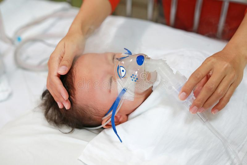 De baby heeft astma en behoeftenebulizations, de Zieke therapie van de jongensinhalatie door het masker van inhaleertoestel De ba stock foto