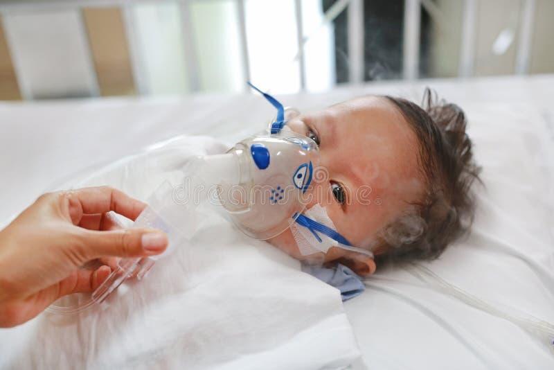 De baby heeft astma en behoeftenebulizations, de Zieke therapie van de jongensinhalatie door het masker van inhaleertoestel De ba royalty-vrije stock afbeeldingen