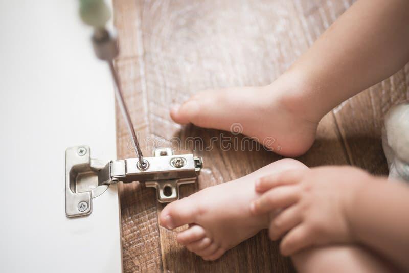 De baby herstelt de kabinetsdeur met een schroevedraaier royalty-vrije stock afbeelding